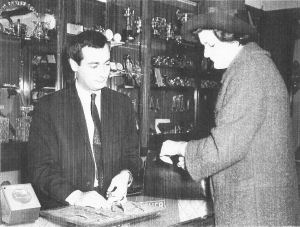 Mr Robin Juste attends to a customer at Bowden & Sons Ltd, Plymouth, 1960.
